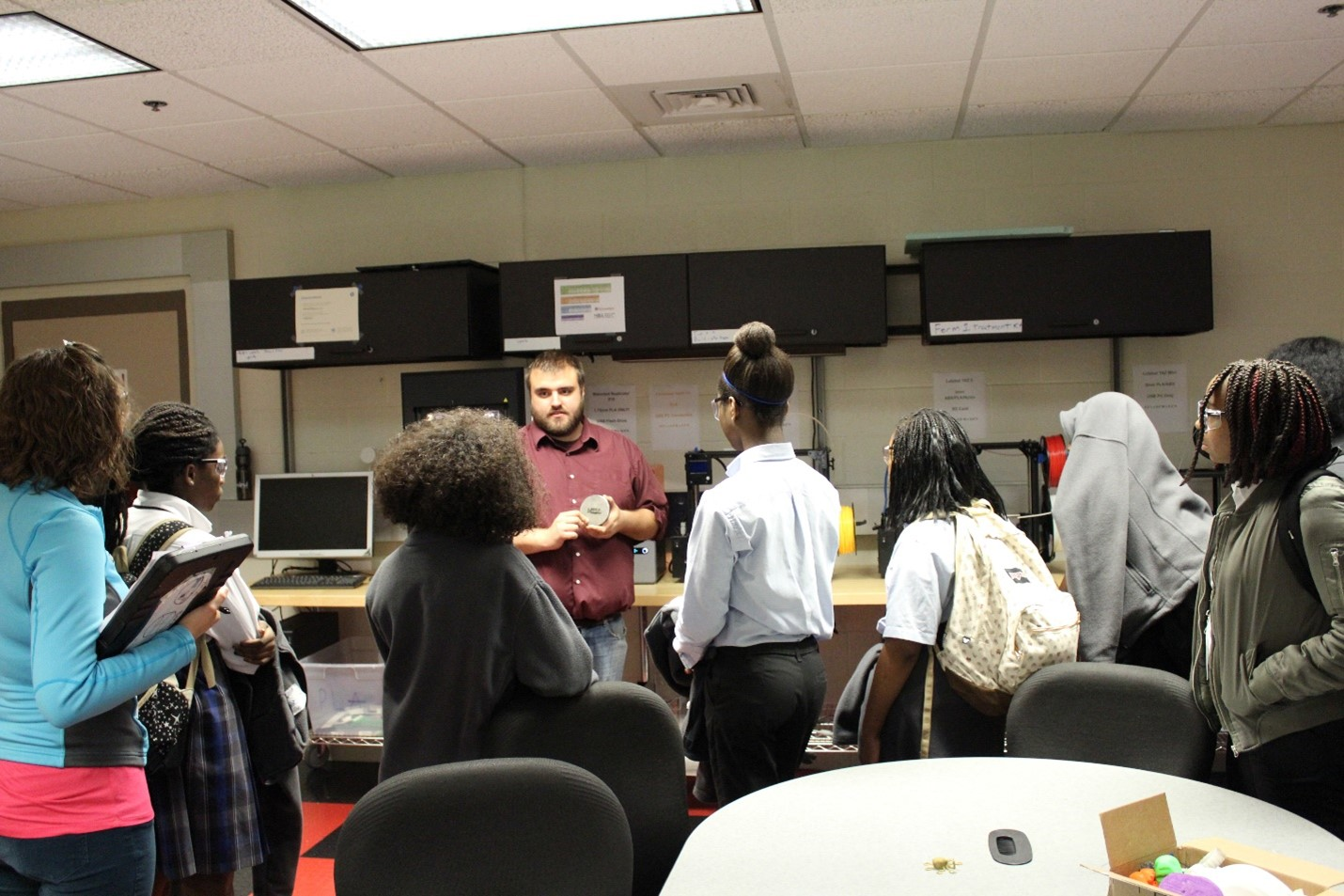 Students surround a professor introducing a lab